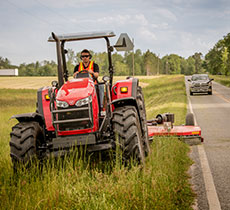 Tractor Cutting Grass On Highway