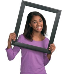 Girl posing for school picture and holding frame in front of face