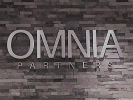 OMNIA Partners logo hanging on a brick wall