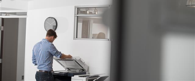 man using xerox printer from afar