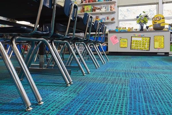 blue carpet under desks in a classroom