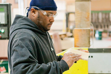 man checking piece of wood just cut