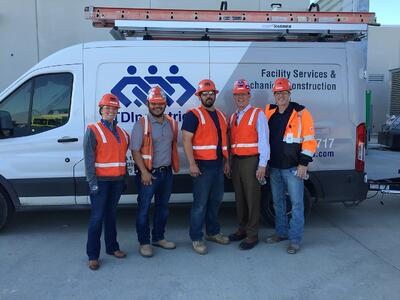 Group of construction workers posing in front of TDIndustries van