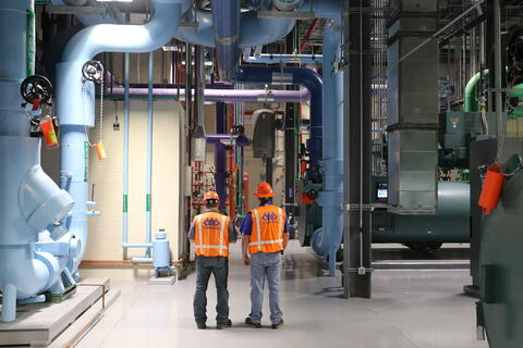 construction workers working with mechanical machinery