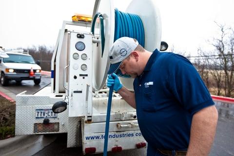 plumber using hose on back of truck