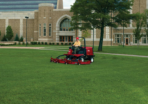 man mowing grass on college campus