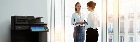 women conversing near copy machine