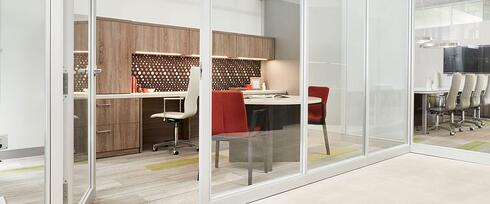 small office setup inside room with glass walls