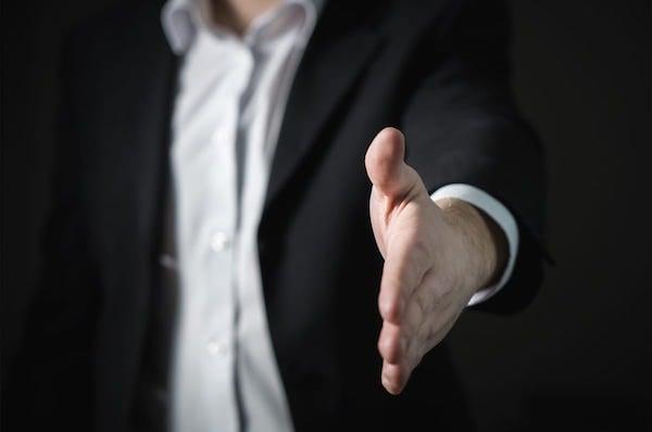 Man In Suit Reaching For Handshake