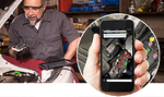 mechanic using a cellphone to help with car diagnostic tests